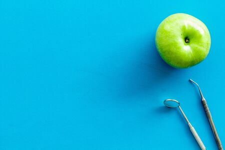 dentist desk with instruments and apple on blue background top view mock-up