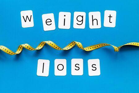 Weight loss text with measuring tape on blue background top view