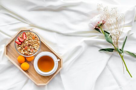 Breakfast on the tray with granola, tea and fruit on white bed sheet background top view Stock Photo