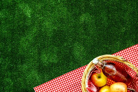 basket for picnic with apples, drink on green textured background top view copy space Stock Photo