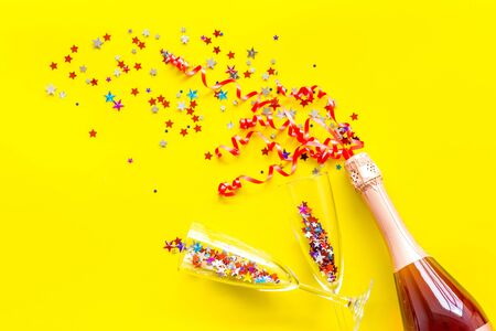 Party with champagne bottle, glasses and colorful party streamers on yellow background top view