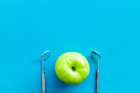Dentist tools for cure teeth and apple on blue background top view copy space