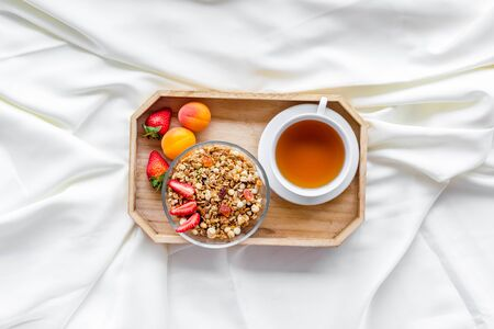 granola, tea and fruit for homemade breakfast on the tray on white bed sheet background top view Stock Photo