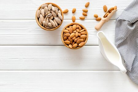 Almond milk with almonds on white wooden background top view copyspace