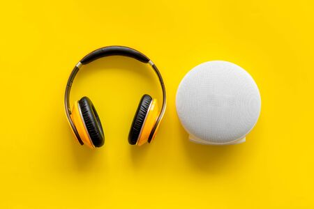 Wireless headphones and portable speaker on yellow background top view copyspace Stockfoto