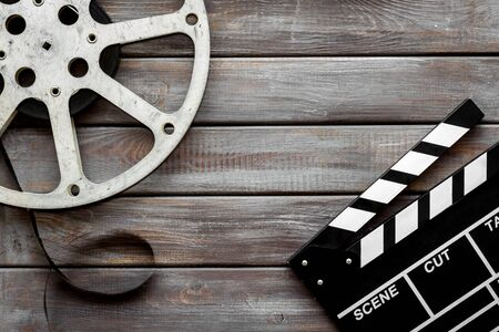 Go to the cinema with film type and clapperboard on wooden background top view Banque d'images - 127997294