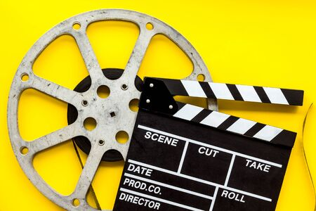 Filmmaker profession with clapperboard and video tape on yellow background top view Banque d'images - 127997320