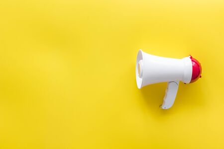 Attract attention with megaphone on yellow background top view copyspace Reklamní fotografie
