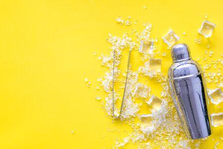 Eiswürfel und Shaker auf gelbem Tischplatten-Mock-up