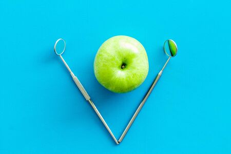 Dentist tools for cure teeth and apple on blue background top view