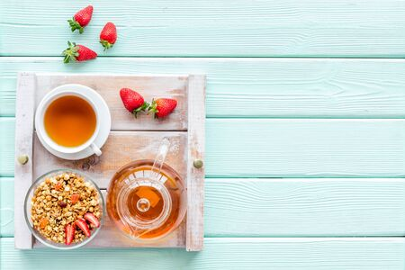 Breakfast on the tray with granola, tea and fruit on mint green wooden background top view mock up