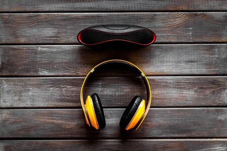 Music and gadget with wireless headphones and portable speaker on wooden background top view