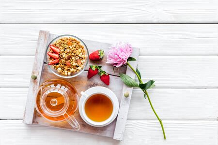 granola, tea and fruit for homemade breakfast on the tray on white wooden background top view Stock Photo