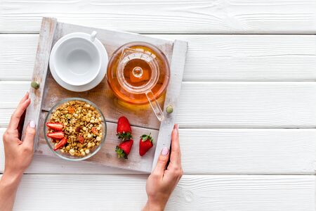 Breakfast on the tray in hands with granola, tea and fruit on white wooden background top view mock up