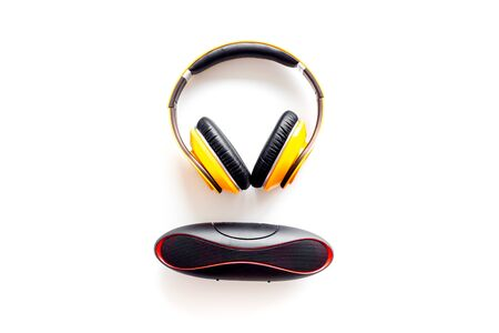 Music and gadget with wireless headphones and portable speaker on white background top view