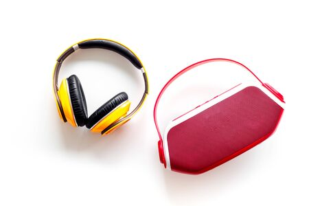 Wireless headphones and portable speaker on white background top view