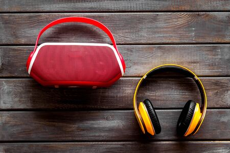 Wireless headphones and portable speaker on wooden background top view