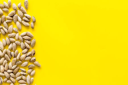 Healthy snack. Almond for cooking on yellow background top view mockup