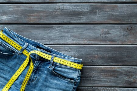 pants and measuring tape for weight loss and building of body shape on wooden background top view mockup.