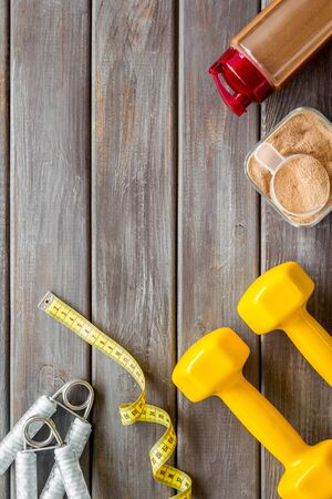Diet for workout in gym. Sports nutrition with scoop and protein, shaker, bars, tape on wooden background top view space for text