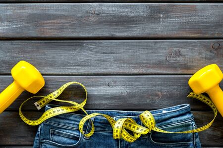 pants, bars and measuring tape for weight loss on wooden background top view space for text