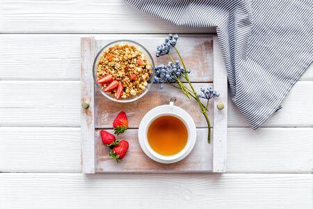 Frühstück auf dem Tablett mit Müsli, Tee und Obst auf Draufsicht des weißen hölzernen Hintergrundes