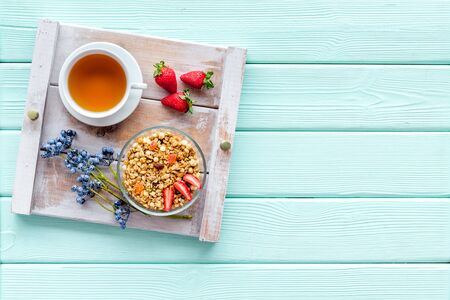 Breakfast on the tray with granola, tea and fruit on mint green wooden background top view mockup