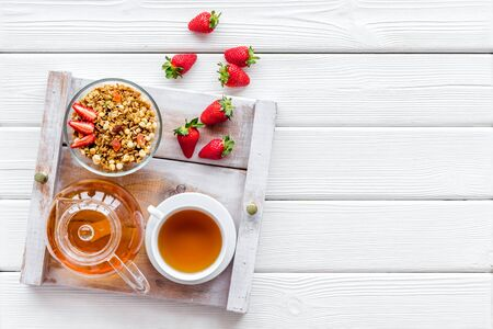 Breakfast on the tray with granola, tea and fruit on white wooden background top view mock up Stock Photo