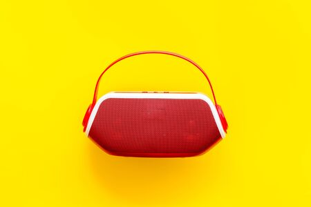 Wireless speaker as music gadgets on yellow background top view