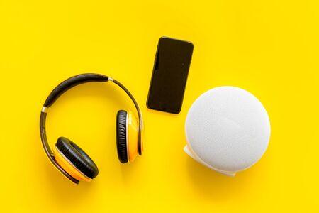 altoparlanti wireless portatili, telefono e cuffie per l'ascolto di musica su sfondo giallo vista dall'alto