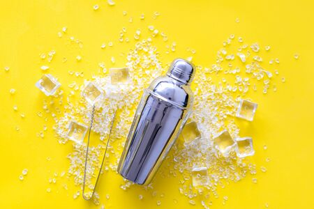 Frozen water in ice cubes and shaker on yellow bar table top view Stock Photo