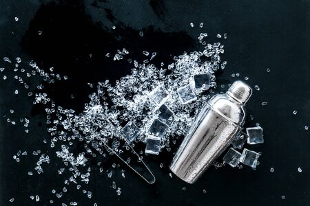 Frozen water in ice cubes and shaker on black bar table top view