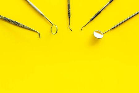 Dentist work desk with tools for teeth on yellow background top view copyspace