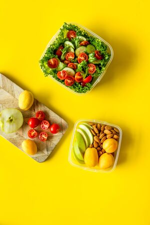 Meal in lunch box to take away on yellow background top view