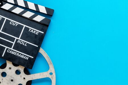 Movie premiere concept with clapperboard, film type on blue background top view space for text
