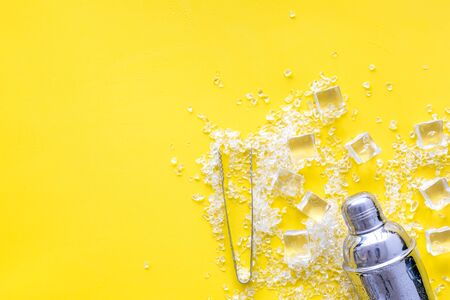 Frozen water in ice cubes and shaker on yellow bar table top view mock-up Banco de Imagens