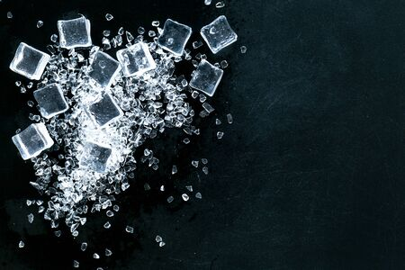 Frozen water in ice cubes on black bar table top view mock up Banco de Imagens