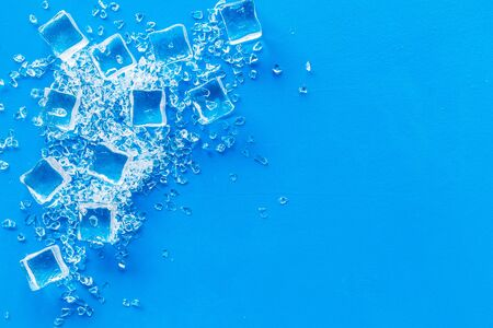 Frozen water in ice cubes on blue bar table top view mock up