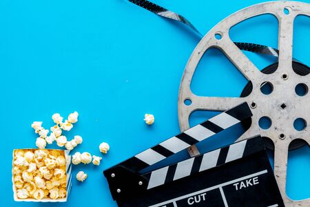 Go to the cinema with popcorn, film type and clapperboard on blue background top view mock-up