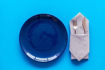 Table setting with plates and flatware on blue background top view Archivio Fotografico - 128388918