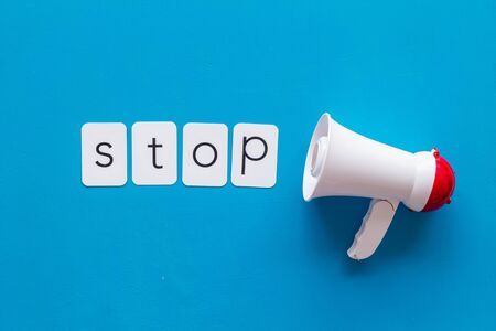 Stop announcement symbol with megaphone and text on blue background top view