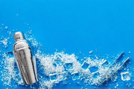 Frozen water in ice cubes and shaker on white bar table top view copy space Banco de Imagens
