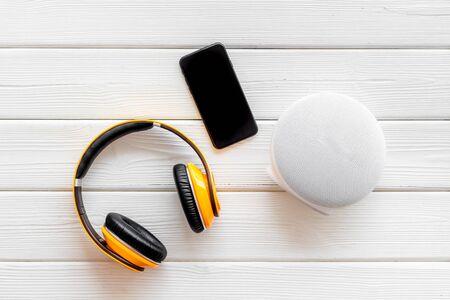 Altavoces inalámbricos portátiles, teléfono y auriculares para escuchar música en la vista superior de fondo de madera blanca