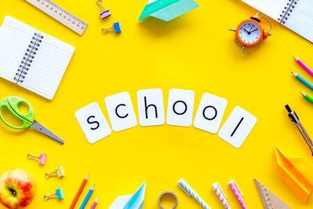 Education concept with school word and frame of stationery with notebook, pens, clock on yellow background top view