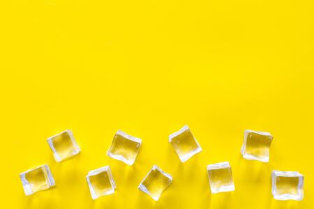Frozen water in ice cubes on yellow bar table top view mock up
