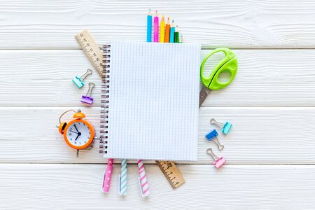 Education concept with stationery of student with notebook, pens, clock on white wooden background top view mock up