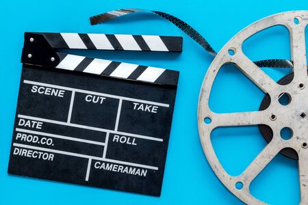 Go to the cinema with film type and clapperboard on blue background top view Banque d'images - 128386009