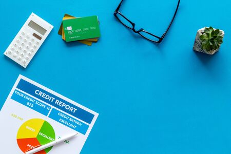 credit report with credit cards and calculator, glasses on banker work place blue background top view mock up Imagens