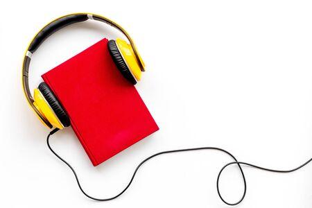 Escuche audiolibros con auriculares sobre fondo blanco. flatlay mock up