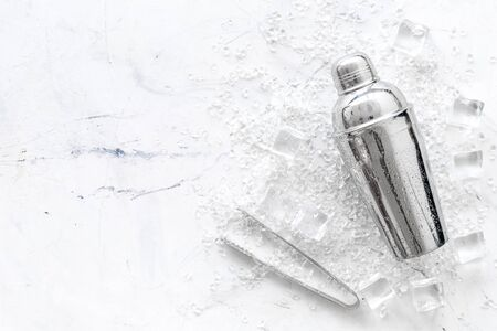 Frozen water in ice cubes and shaker on marble bar table top view mockup
